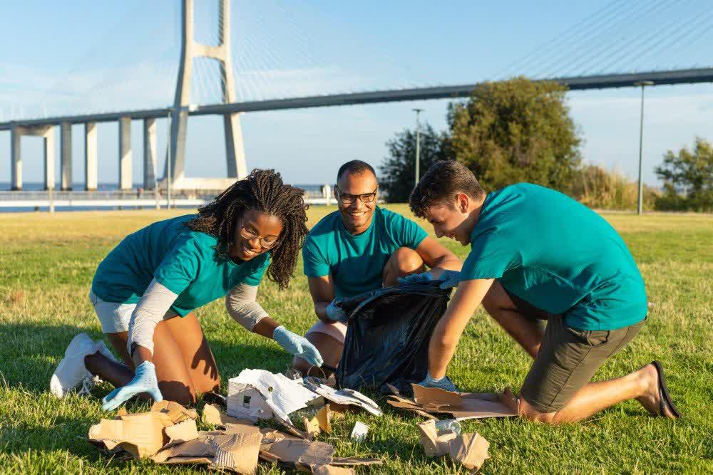 Trois bénévoles nettoient et trient les ordures près de la ville