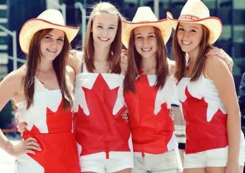 Quatre jeunes filles canadiennes portant des vêtements avec le drapeau canadien
